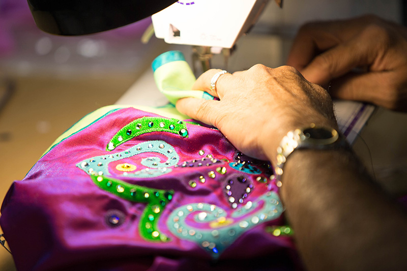 Wardrobe staff sewing sequins on ensamble costume